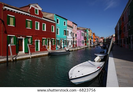 Canal on the island of Burano, near Venice, Italy. The multi-colored houses set the village on this island apart from the city of Venice. - stock photo