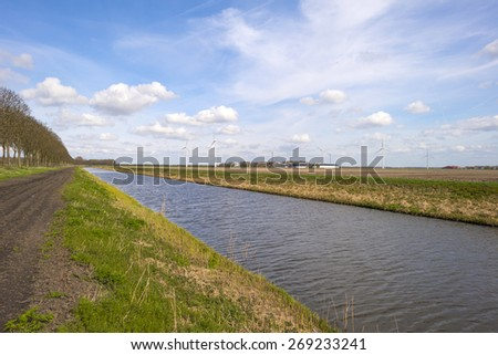 Canal under a blue cloudy sky in spring - stock photo