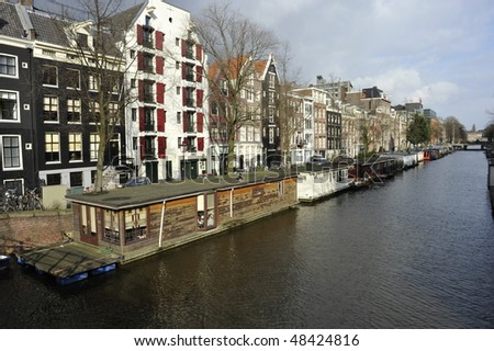 canal water reflecting Dutch buildings boat houses clouds and blue sky - stock photo