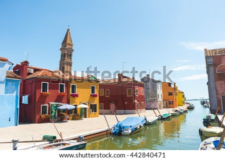 Canal with colorful houses, church, boats and bridge on the famous island Burano, view from the sea, Venice, Italy, Europe - stock photo