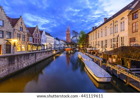 Canals of Bruges with the church of our lady in the background. - stock photo