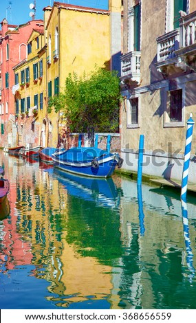 Canals of Venice at sunny day with boats and reflection in water, Italy - stock photo