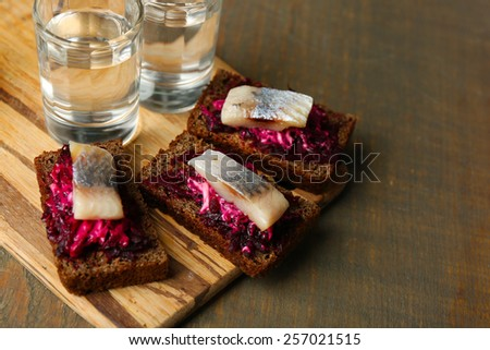 Canape herring with beets on rye toasts, on wooden board, and glass of vodka on wooden table background - stock photo
