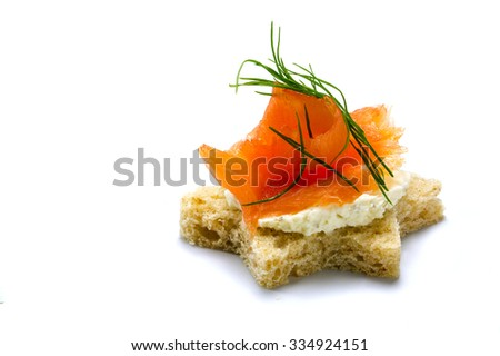 canape in star shape with smoked salmon on horseradish cream and dill garnish for a Christmas buffet, isolated on a white background - stock photo