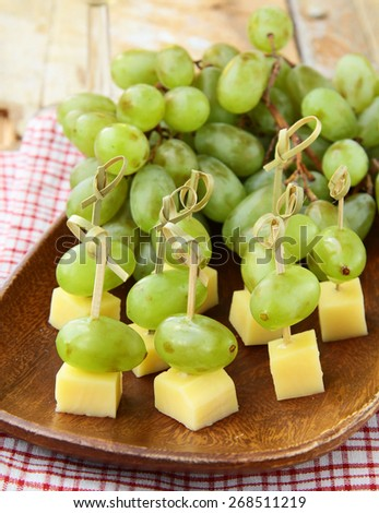 canape snack - cheese with green grapes on wooden skewers - stock photo