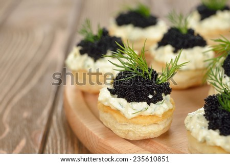 Canape with caviar on a brown background - stock photo