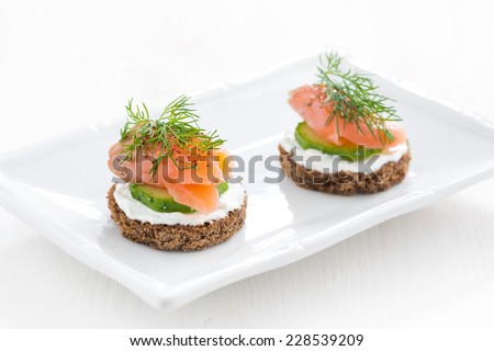 canape with cheese, cucumber and salted salmon on a plate - stock photo