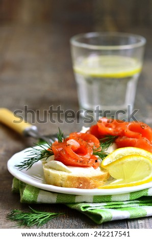 Canape with homemade salted salmon and curd on a plate. - stock photo
