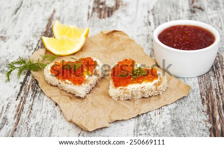 canape with red caviar on a old wooden background - stock photo