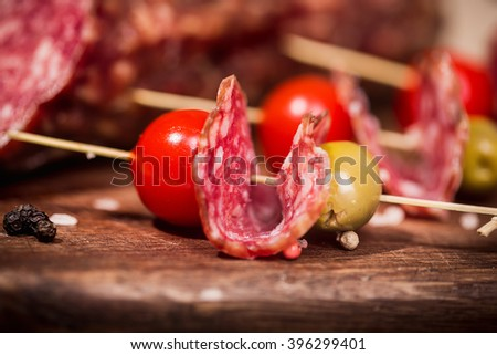 canape with salami, tomato and olive - stock photo