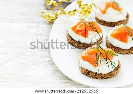 canape with salmon and cream cheese on a light background. tinting. selective focus on the first canape - stock photo