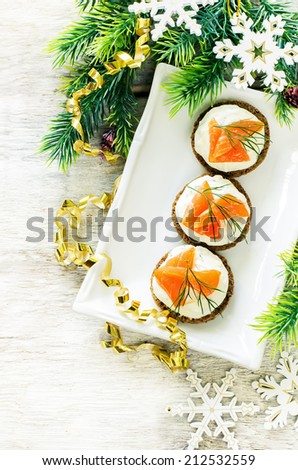 canape with salmon and cream cheese on a light background. tinting. selective focus on the middle canape - stock photo