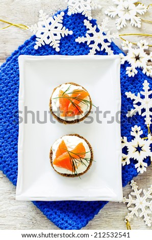 canape with salmon and cream cheese on a light background. tinting. selective focus on the top canape - stock photo