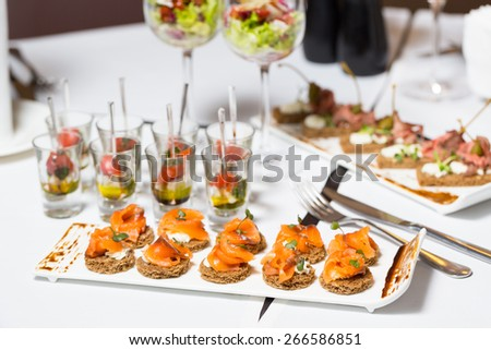 canape with salmon on a white plate,catering weddings table with - stock photo