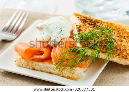 Canape with smoked salmon and dill sauce on plate - stock photo