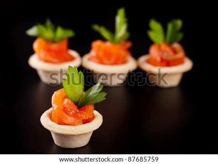 Canape with smoked salmon fish on black background - stock photo