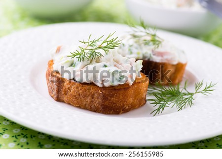 Canape with soft cheese spread on white plate, close up, selective focus - stock photo