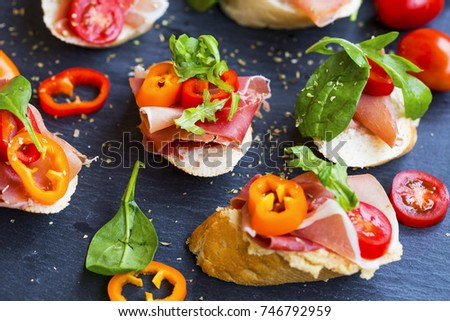 Canapes appetizer with prosciutto ham, pepper slices, tomatoes and green spinach and rucola leaves, healthy crostini or bruschettas italian appetizer seasoned