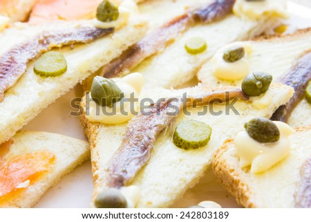 Canapes with anchovy and capers - stock photo