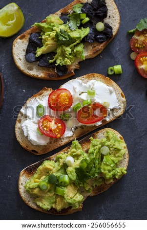 Canapes with avocado spread, goat cheese and black garlic - stock photo