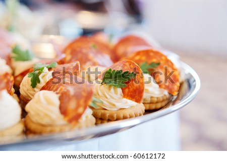 Canapes with choriso wurst on table - stock photo