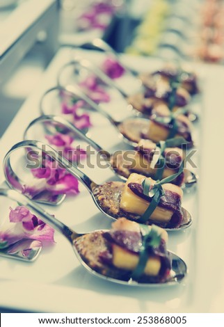 Canapes with cured ham (jamon or prosciutto) on banquet table, selective focus, toned image - stock photo