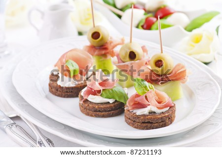 Canapes with ham and green pickled olives - stock photo