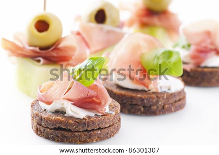 canapes with ham and pickled olives - stock photo