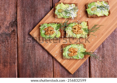Canapes with paste of avocado, walnuts, cheese and sesame seeds. The concept of the restaurant, a healthy diet food. Snack of canapes with avocado, nuts and herbs on a kitchen board.  - stock photo