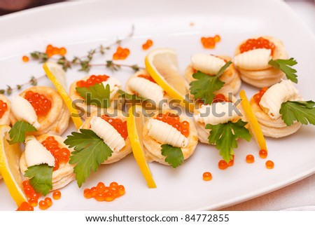 Canapes with red caviar and lemon