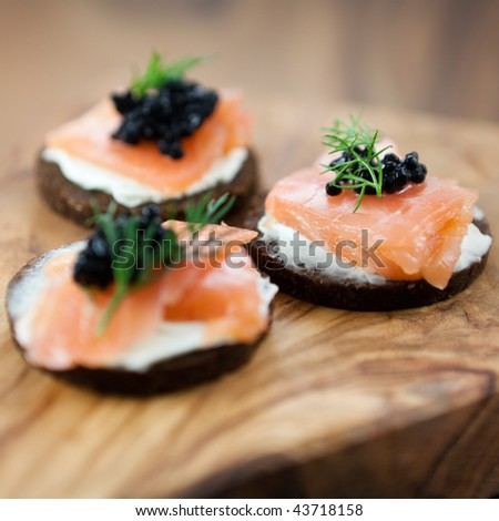 Canapes with salmon and caviar - stock photo