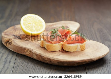 canapes with salmon, dill and lemon on wood table - stock photo