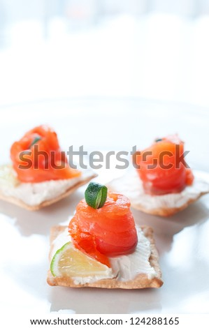 Canapes with smoked salmon and cream cheese on white plate - stock photo