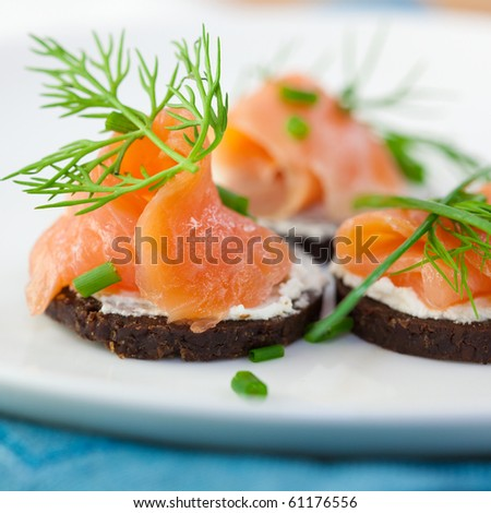 Canapes with smoked salmon and herbs - stock photo
