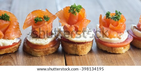 canapes with smoked salmon on wooden table