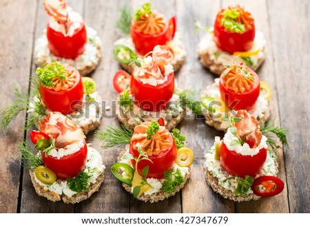 Canapes with stuffed cherry tomatoes  - stock photo