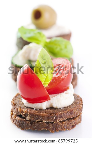 Canapes with tomato and olives - stock photo