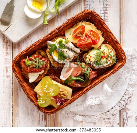 Canapes with various toppings, delicious breakfast or snack - stock photo