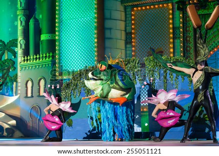 CANARY ISLAND, SPAIN - FEBRUARY 20, 2015: Drag Noa (m) with frog costume and unidentified assists as flowers or plants performing onstage during city of Las Palmas carnival Drag Queen Gala. - stock photo