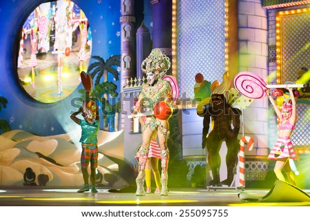 CANARY ISLAND, SPAIN - FEBRUARY 20, 2015:Drag Vulcano with costume from Isidro Javier Perez Mateo and unidentified assistants with lollipops onstage during city of Las Palmas carnival Drag Queen Gala. - stock photo