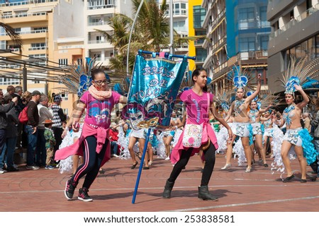 CANARY ISLAND, SPAIN - FEBRUARY 17, 2015: Unidentified girls from Brisa de Volcan with the dancing-goup banner in the streets during city of Las Palmas carnival in the sun. - stock photo