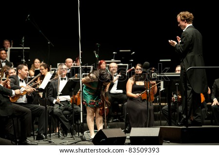 CANARY ISLANDS – AUGUST: 03: Violinist Carla Marrero, only 16 years, from Spain, and Conductor Michael Zlabinger from US, onstage, during Festival of Music August 03, 2011 in Canary Islands, Spain - stock photo