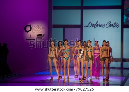 CANARY ISLANDS - 18 JUNE: Models wearing swimwear from Dolores Cortez Summer Collection at Moda Calida in Maspalomas June 18, 2011 in Canary Islands, Spain - stock photo