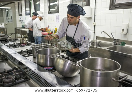 CANARY ISLANDS, SPAIN - JUNE 27, 2017: Photo with motion blur of a cook adding vegetables to a pot