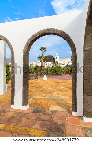 Canary style building with view of apartments in marina Rubicon thorough arches, Lanzarote, Canary Islands, Spain - stock photo