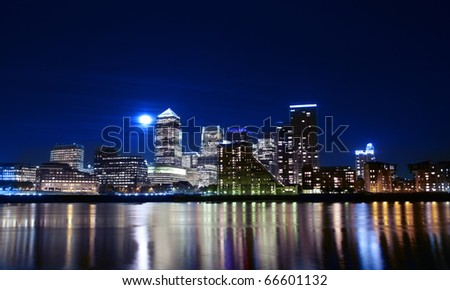 Canary wharf across the Thames at night long exposure by moonlight