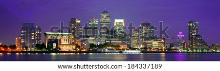 Canary Wharf business district in London at night over Thames River.  - stock photo