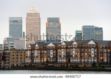 Canary Wharf, London, England, UK, at dusk with some typical Thames waterfront residential buildings in the foreground