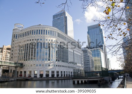 Canary Wharf skyscrapers in London with reflections in the river - stock photo