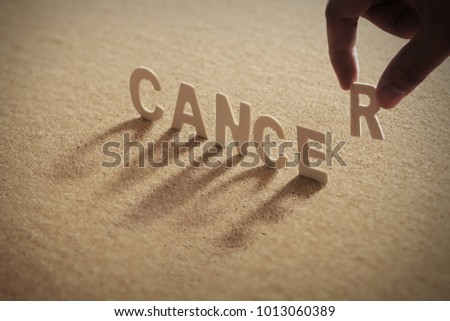 CANCER wood word on compressed or corkboard with human's finger at R letter.